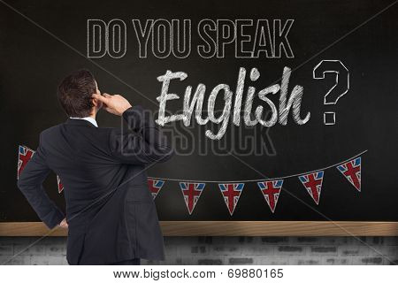 Thinking businessman scratching head against blackboard on wall