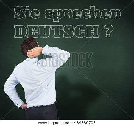 Thinking businessman scratching head against green chalkboard, Do you speak German?