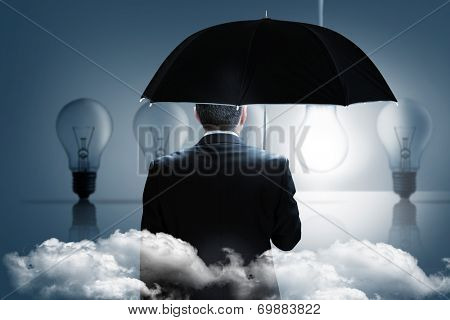 Mature businessman holding an umbrella against five light bulbs in a row with one lit up