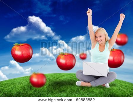 Joyful woman with a notebook against green field under blue sky