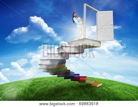 Side view of young woman carrying a pile of books against green hill under blue sky