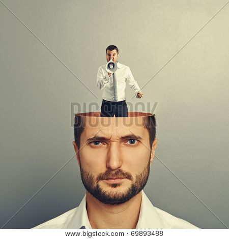 small screaming and angry man with megaphone in the head of young serious man over grey background