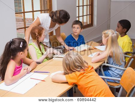 Pretty teacher standing with pupils at desk at the elementary school
