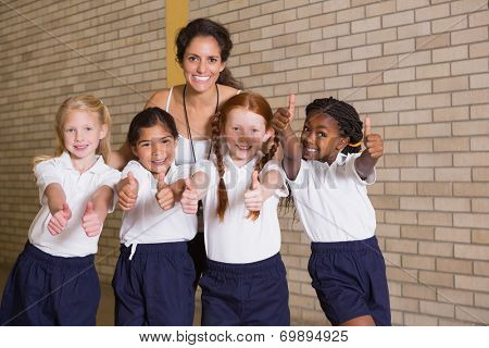 Cute pupils smiling at camera in PE uniform at the elementary school