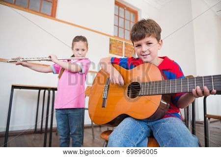 Cute pupils playing flute and guitar in classroom at the elementary school