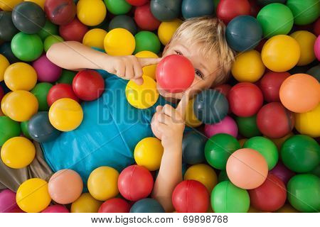 Happy boy playing in ball pool at a party