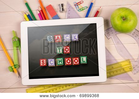 Composite image of digital tablet on students desk showing back to school message