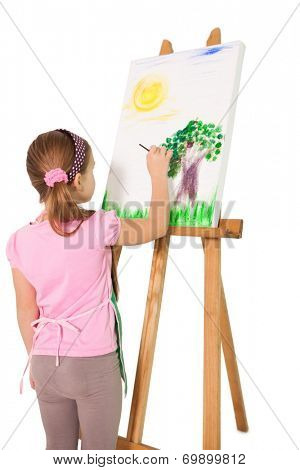 Happy little girl painting on easel on white background