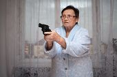 stock photo of scared  - Scared senior woman aiming a gun indoors - JPG