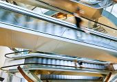 stock photo of escalator  - People in motion in escalators at the modern shopping mall - JPG