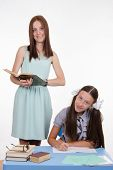 stock photo of diligent  - Teacher standing at desk behind which sits a diligent student - JPG
