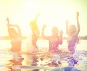 pic of teenagers  - Group of happy teen girls playing in water at the beach on sunset - JPG