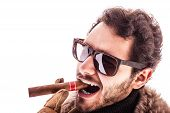 stock photo of hustler  - a young and rich man wearing a sheepskin coat isolated over a white background holding a cigar - JPG