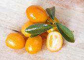 stock photo of kumquat  - fresh kumquat  just picek  over wooden baclground - JPG