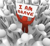 pic of daring  - I Am Brave words on a sign held by one man in a crowd showing he is unique and different in being bold - JPG