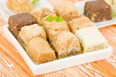 stock photo of phyllo dough  - Baklava - Middle Eastern sweet pastry and nuts selection on an orange background. ** Note: Shallow depth of field - JPG