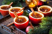stock photo of cider apples  - Apple cider with cinnamon sticks and anise star in apple cups - JPG