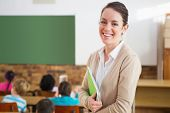 stock photo of teachers  - Pretty teacher smiling at camera at back of classroom at the elementary school - JPG