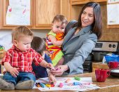 picture of babysitter  - A mother in the kitchen plays with her babies