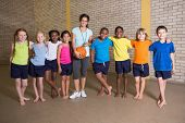 image of physical education  - Cute pupils smiling at camera with PE teacher at the elementary school - JPG
