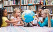 picture of pupils  - Cute pupils looking at globe in library at the elementary school - JPG