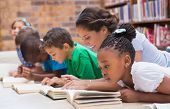 stock photo of pupils  - Cute pupils and teacher lying on floor in library at the elementary school - JPG