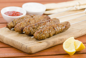 stock photo of raita  - Minced meat kebabs on metal skewers on a wooden board served with cucumber and red onion raita - JPG