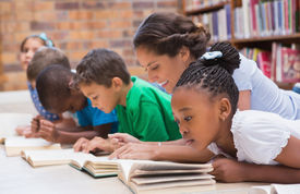 picture of librarian  - Cute pupils and teacher lying on floor in library at the elementary school - JPG