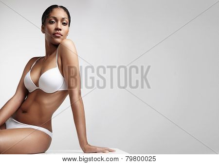 Woman With Beauty Figure Sitting On A Table