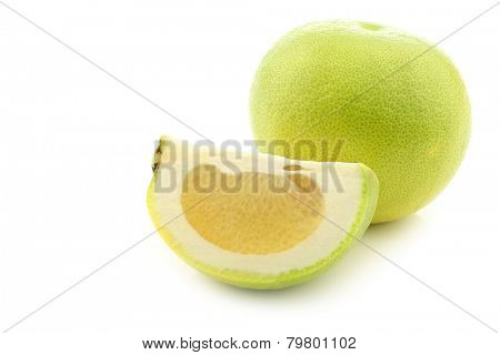 green sweet grapefruit and a cut piece on a white background