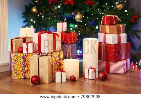Pile of present boxes under Christmas tree on wooden floor, indoors