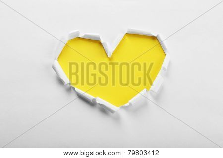 White torn paper heart over yellow background