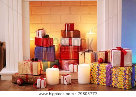Christmas present boxes under fireplace on wooden floor, indoors