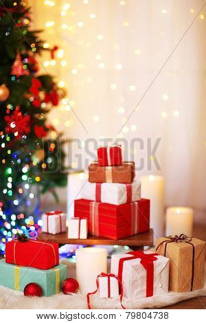 Pile of Christmas present boxes on fur carpet on wooden floor, on bright background