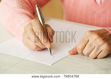 Hands of adult woman writing with pen, on table, on light background