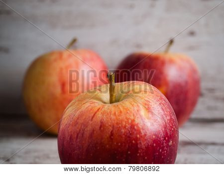 Three Red Apples Over Wooden Background