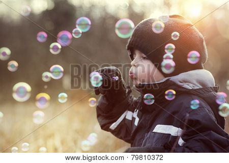 Little boy playing with bubble wand blowing soap bubbles
