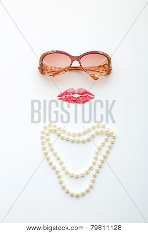Glasses, lips and necklace forming woman face