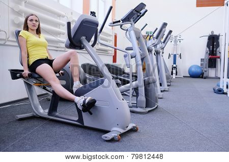 athletic girl is engaged on a stationary bike