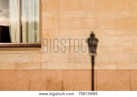 Lamp post shadow on wall of house