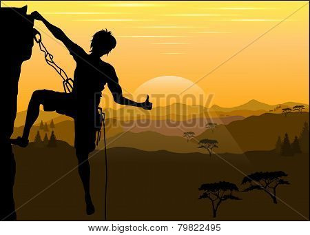 Silhouette Of A Climber On A Rock Against The Evening Mountain Landscape