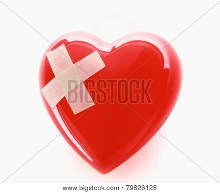 A red heart with adhesive plaster isolated on white background