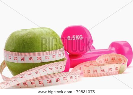 An apple, a measuring tape and dunbbell