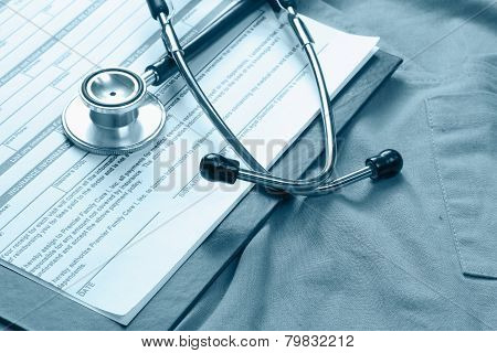 A stethoscope and RX prescription lying on a medical uniform