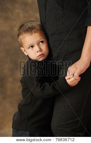 Close-up image of a shy preschooler clinging closely to his mother.  Shallow DOF with focus on boy's face.