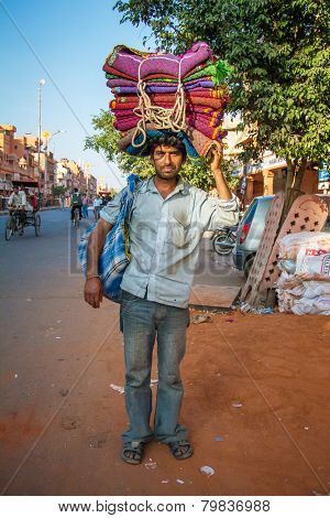 JAIPUR, INDIA - NOVEMBER 25, 2012: Unidentified Indian man carries colorful blankets on his head on November 25, 2012 in Jaipur, Rajasthan, India.