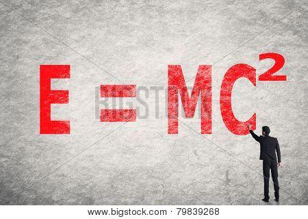 Asian businessman write text on wall, E = mc2