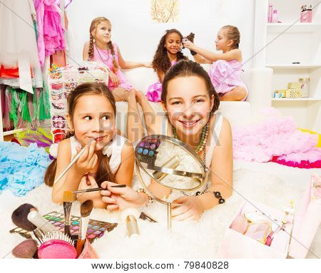 Pretty girls applying make-up with friends behind
