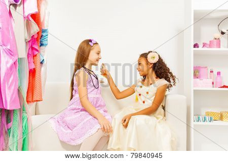 African girl applying perfume  on her friend
