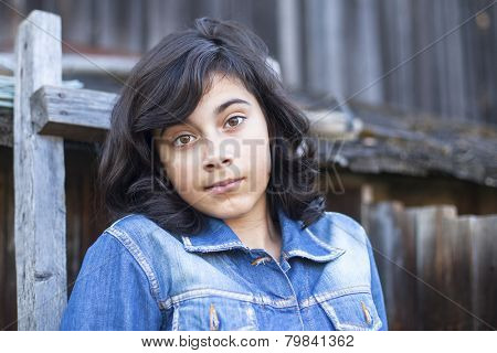 Portrait of a young brunette girl dressed in a denim jacket outdoors in the village.